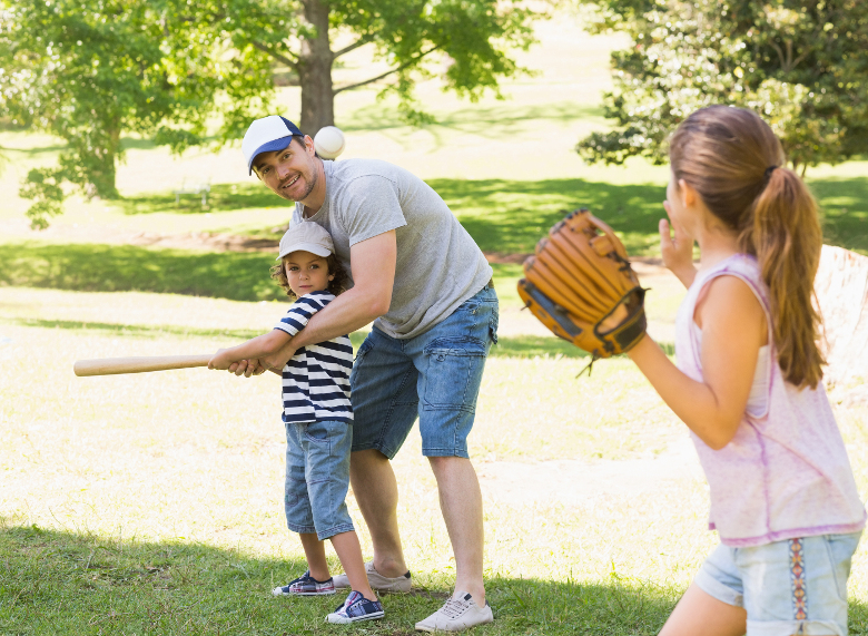 Family of three playing baseball in the park